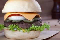 Sluit omhoog van rundvleeshamburger met kaas op houten lijst Royalty-vrije Stock Afbeeldingen