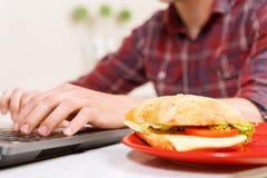 Sluit omhoog van sandwich op plaat en de typende mens Stock Afbeelding