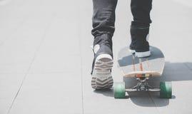 Sluit omhoog van skater& x27; s benen op longboard die bij de straat in openlucht berijden in stock foto's