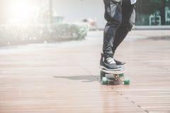 Sluit omhoog van skater& x27; s benen op longboard die bij de straat in openlucht berijden in stock foto