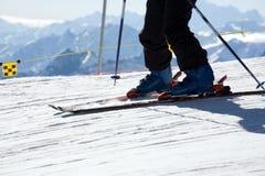 Sluit omhoog van skibenen en skistok tegen berg Royalty-vrije Stock Foto's