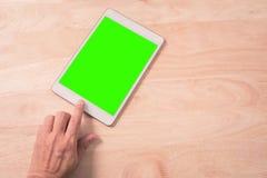 Sluit omhoog van slimme de telefoontablet van de handaanraking met groene achtergrond op hout Stock Foto