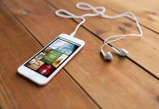 Sluit omhoog van smartphone en oortelefoons op hout royalty-vrije stock foto's