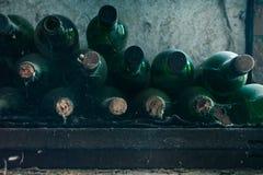 Sluit omhoog van sommige zeer oude en stoffige wijnflessen in een wijnkelder stock afbeelding