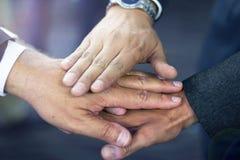 Sluit omhoog van Spaanse bedrijfsmensen toetredende handen stock fotografie