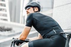 Sluit omhoog van sportman het ontspannen na het berijden van fiets naast moderne wolkenkrabbers royalty-vrije stock afbeelding