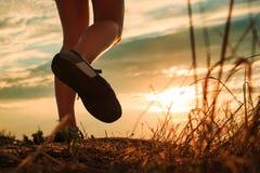 Sluit omhoog van sportwoman voeten in de herfstgras royalty-vrije stock fotografie