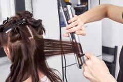 Sluit omhoog van stilist` s hand gebruikend krullend ijzer voor haarkrullen stock foto