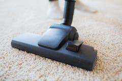 Sluit omhoog van stofzuiger schoonmakend tapijt thuis Stock Afbeeldingen