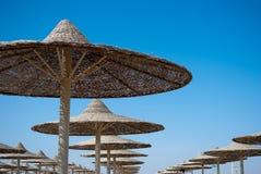 Sluit omhoog van strandparaplu's tegen de duidelijke blauwe hemel royalty-vrije stock afbeelding