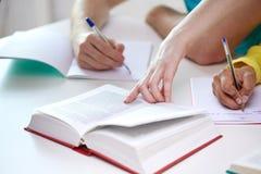 Sluit omhoog van studentenhanden schrijvend aan notitieboekjes Stock Fotografie