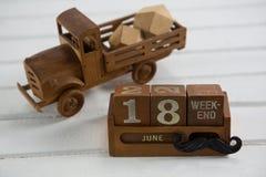 Sluit omhoog van stuk speelgoed vrachtwagen door kalender op lijst Royalty-vrije Stock Foto's