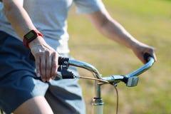 Sluit omhoog van stuur die terwijl het berijden van een fiets worden gehouden stock foto