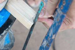 Sluit omhoog van Timmerman die een raad met een hand houten zaag zagen Stock Afbeeldingen