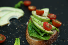 Sluit omhoog van toost met spinaziebladeren, avocado en tomaties Stock Foto