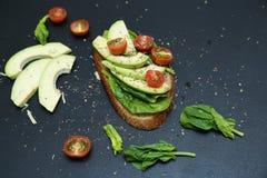 Sluit omhoog van toost met spinaziebladeren, avocado en tomaties Stock Afbeelding