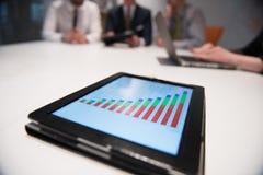 Sluit omhoog van touchpad met analyticsdocumenten bij bedrijfsmeetin Royalty-vrije Stock Foto's