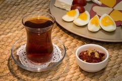 Sluit omhoog van traditioneel Turks thee en voorgerecht met vage mening van ontbijt met kaas, salami, gekookt ei, en tomaat Stock Afbeelding