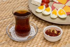 Sluit omhoog van traditioneel Turks thee en voorgerecht met vage mening van ontbijt met kaas, salami, gekookt ei, en tomaat Royalty-vrije Stock Foto