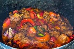 Sluit omhoog van traditionele Oezbekistaanse die shurpaschotel van lam en diverse groenten bij de open brand in gietijzerketel wo Stock Foto