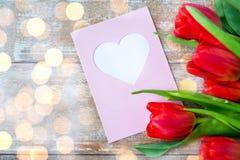 Sluit omhoog van tulpen en groetkaart met hart Royalty-vrije Stock Afbeeldingen