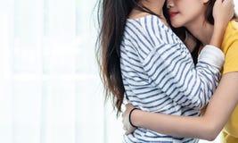 Sluit omhoog van twee Aziatische Lesbische vrouwen die samen in slaapkamer kijken stock foto's
