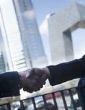 Sluit omhoog van twee bedrijfsmensen die handen schudden door het kabeltelevisie-Gebouw in Peking Stock Foto