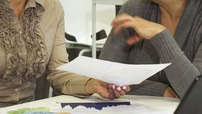 Sluit omhoog van twee bedrijfsvrouwen die documenten bespreken op het kantoor stock videobeelden