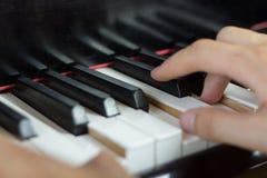 Sluit omhoog van twee handen spelend piano Stock Foto