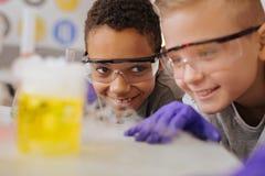 Sluit omhoog van twee klasgenoten die chemische reactie waarnemen royalty-vrije stock afbeelding