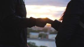 Sluit omhoog van twee minnaars die bij handen aansluiten zich Het paar in liefdeholding overhandigt de stadszonsondergang en kijk stock footage