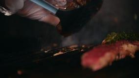 Sluit omhoog van twee plakken van vlees van variërende graden van bereidheid liggen op de grill, chef-kok die één van hen draaien stock videobeelden
