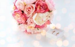 Sluit omhoog van twee trouwringen en bloembos Stock Afbeeldingen