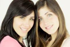 Sluit omhoog van twee vrouwen die camera het glimlachen bekijken stock foto's