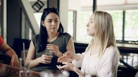 Sluit omhoog van twee vrouwen die in koffie zitten die aan elkaar en drinkwater door het stro spreken Groep jongelui stock video