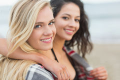 Sluit omhoog van twee vrouwen omvat met deken bij strand Royalty-vrije Stock Afbeelding