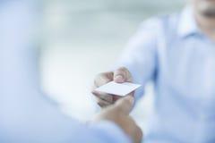 Sluit omhoog van twee zakenlieden die adreskaartjes ruilen Royalty-vrije Stock Foto