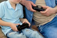 Sluit omhoog van vader en zoons het spelen videospelletje Stock Afbeelding