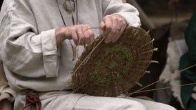 Sluit omhoog van vakman die landelijke kleren dragen makend rieten mand van takjes Traditionele met de hand gemaakte het weven te stock footage