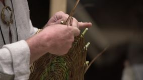 Sluit omhoog van vakman die landelijke kleren dragen makend rieten mand van takjes Traditionele met de hand gemaakte het weven te stock video