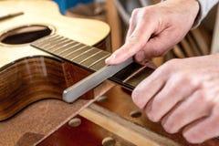 Sluit omhoog van vakman` s handen, indienend de lijstwerken van een gitaar stock afbeeldingen