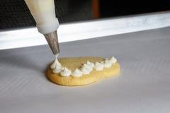 Sluit omhoog van vanille die wordt door buizen geleid op een hart gevormd suikerkoekje berijpen royalty-vrije stock afbeelding