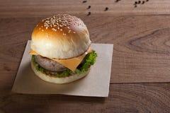 Sluit omhoog van varkensvleeshamburger met kaas op houten lijst Stock Afbeeldingen