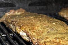 Sluit omhoog van varkensvleesribben met barbecuesaus op de grill Stock Afbeeldingen