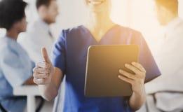 Sluit omhoog van verpleegster met tabletpc die duimen tonen Royalty-vrije Stock Afbeelding