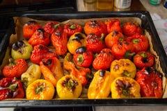Sluit omhoog van vers gebakken in het het bakseldienblad van oven rode en gele peppersin stock afbeelding