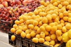 Sluit omhoog van verse data en druiven op markttribune Royalty-vrije Stock Afbeelding