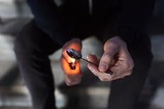 Sluit omhoog van verslaafde die de drug van de barstcocaïne voorbereiden stock foto