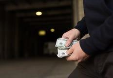 Sluit omhoog van verslaafde of drugdealerhanden met geld Stock Fotografie