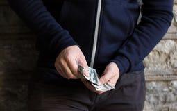 Sluit omhoog van verslaafde of drugdealerhanden met geld Royalty-vrije Stock Fotografie
